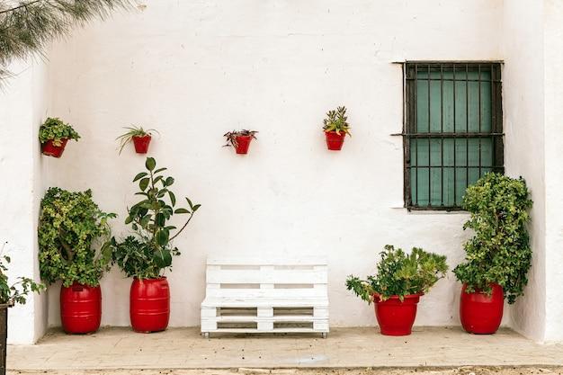 Bella facciata bianca di una tipica casa andalusa in spagna con piante in vasi di argilla rossa