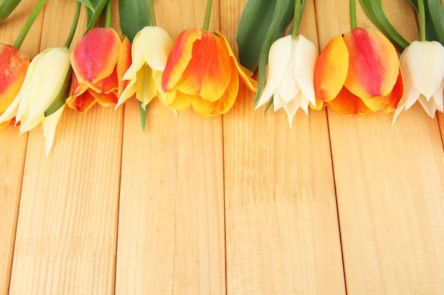 Bei tulipani bianchi e arancioni su legno