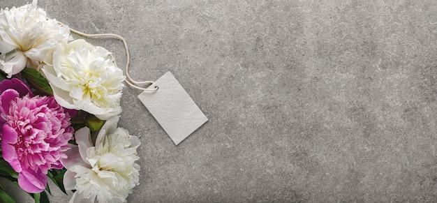 Bellissimi fiori di peonia bianca e tag sul muro di pietra grigia, copia spazio per il tuo testo o design, vista dall'alto, piatto laici