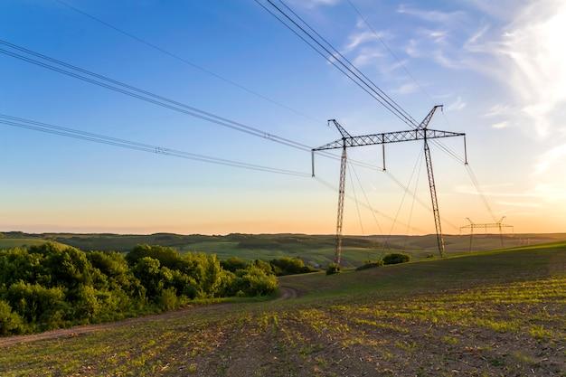 Bellissimo ampio panorama di linee ad alta tensione e piloni di potenza che si estende attraverso i campi di primavera sopra il gruppo di alberi verdi all'alba o al tramonto. trasmissione e distribuzione del concetto di elettricità.