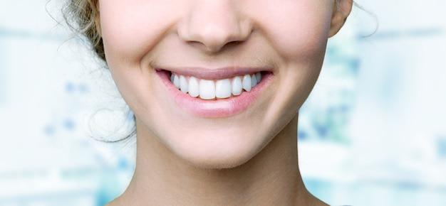Bello ampio sorriso di giovane donna fresca con grandi denti bianchi sani. isolato su sfondo
