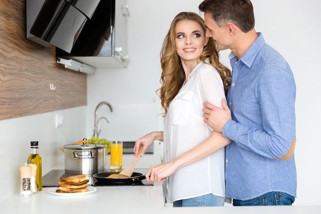Bella moglie che prepara frittelle e flirta con il suo bel marito in cucina