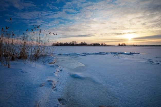 Bellissimo paesaggio invernale con lago ghiacciato e cielo al tramonto. composizione della natura.