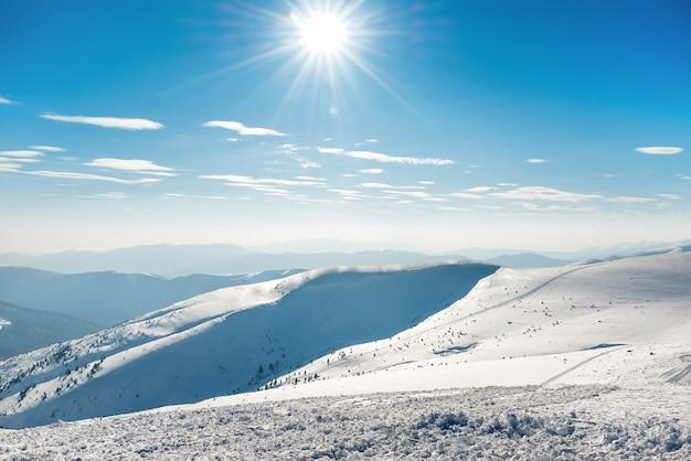 Bellissimo paesaggio invernale con montagne di neve sotto il cielo blu blue