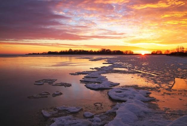 Bellissimo paesaggio invernale con cielo infuocato al tramonto e lago ghiacciato. composizione della natura.