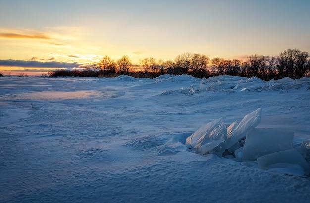 Bellissimo paesaggio invernale con cielo infuocato al tramonto e lago ghiacciato vicino alla riva. composizione della natura.