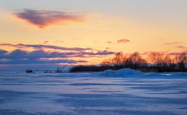 Bellissimo paesaggio invernale con cielo infuocato al tramonto e lago ghiacciato.