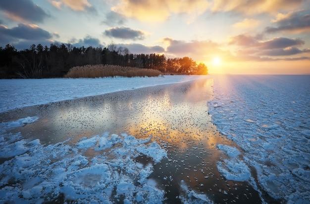 Bellissimo paesaggio invernale con cielo al tramonto e lago ghiacciato