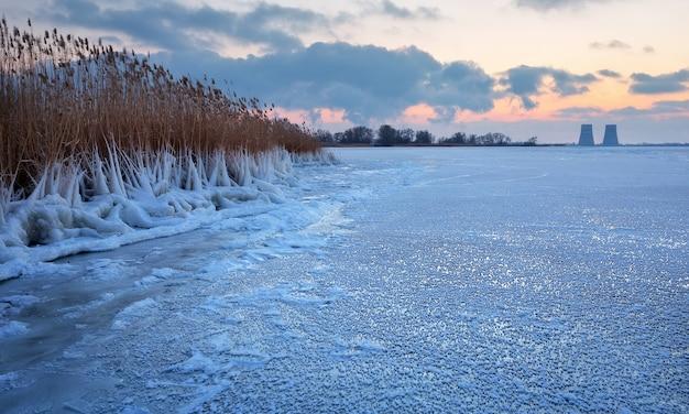 Bellissimo paesaggio invernale con serbatoio congelato cielo al tramonto e centrale elettrica.