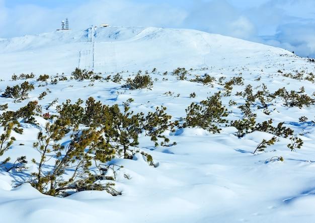 Bellissimo paesaggio montano invernale con impianto di risalita e pista da sci sul pendio