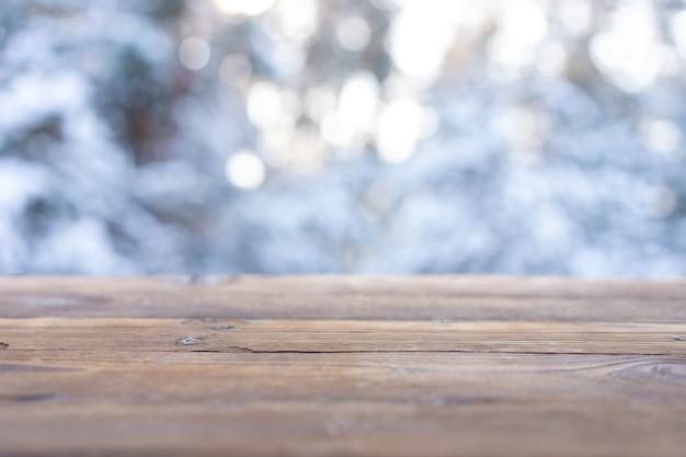 Bella scena invernale. sfondo sfocato dello sfondo della natura di natale innevato, piano del tavolo in legno su bokeh lucido. per l'esposizione del prodotto mock up di natale