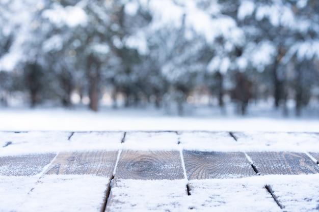 Bella scena invernale. sfondo sfocato dello sfondo della natura di natale innevato, piano del tavolo in legno su bokeh lucido. per l'esposizione del prodotto mock up del periodo natalizio