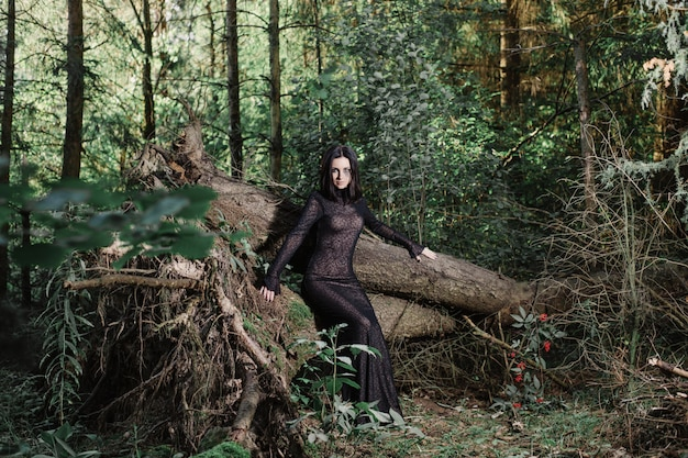 Bella strega in posa in una foresta mistica