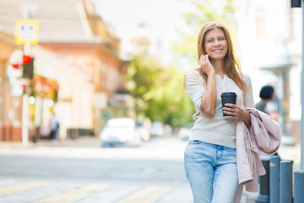 Bella donna di 30 anni che cammina in città in una giornata di sole con una tazza di caffè caldo