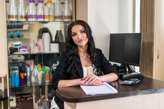 Amministratore di bella donna nel salone di bellezza sul posto di lavoro