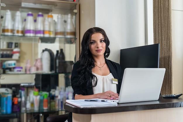 Bella donna amministratore nel salone di bellezza sul posto di lavoro
