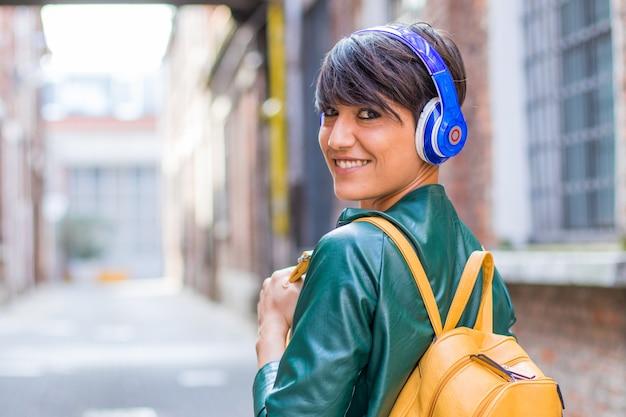 La bella donna sta ascoltando musica con le cuffie