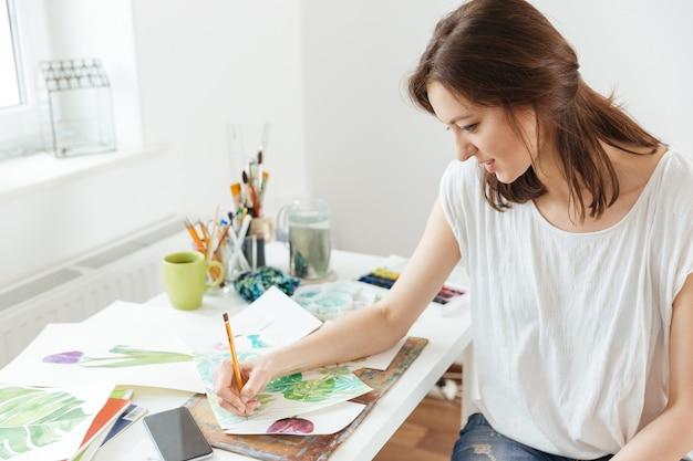 Bella artista donna seduta e disegno al tavolo in officina