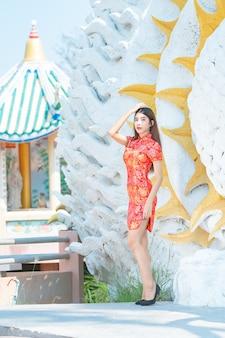 Bella donna asiatica che indossa un abito rosso nel capodanno cinese
