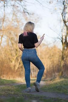 Bella donna nel paesaggio autunnale giovane hipster che tiene il telefono cellulare.