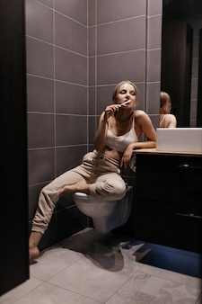 Bella donna in bagno si lava i denti con uno spazzolino da denti