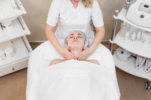 La bella donna dell'estetista esegue le procedure spa, il massaggio facciale e la maschera per la pelle.