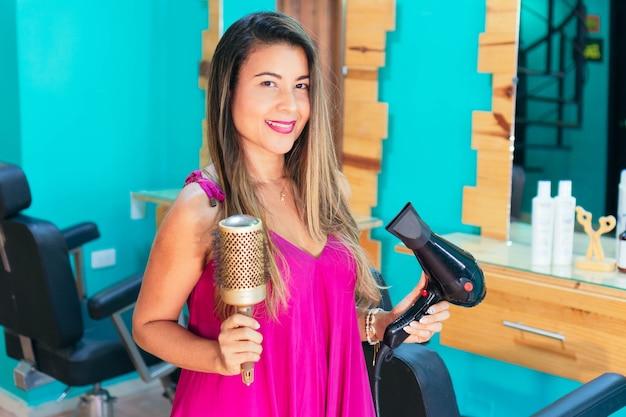 Bella donna nel salone di bellezza che tiene spazzola per capelli e asciugacapelli.