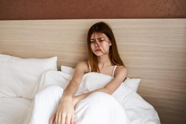 Bella donna a letto sotto le coperte che allunga il modello di interni di design di mattina