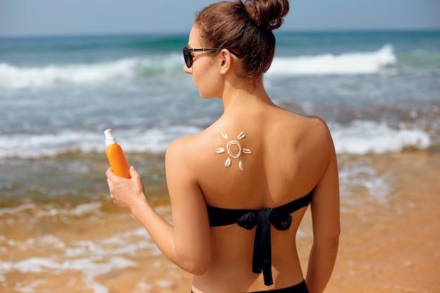 Bella donna in bikini che applica crema solare sulla spalla abbronzata.