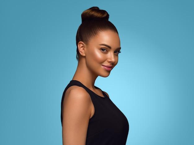 Bella donna abito nero classico taglio di capelli bob su sfondo di colore blu
