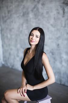 Bella donna in abito nero. su sfondo scuro.