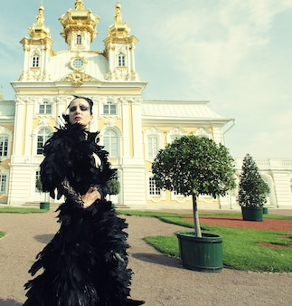 Bella donna in abito nero in posa accanto al palazzo