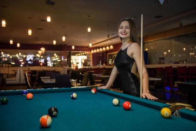 Bella donna in abito nero in posa con stecca da biliardo