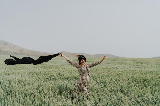 Giorno ventoso dei bei campi di grano dei capelli neri della donna