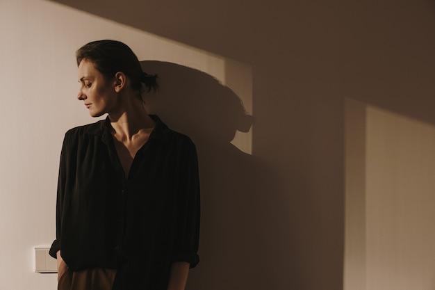 La bella donna in camicia nera e pantaloni marroni sta contro il muro.
