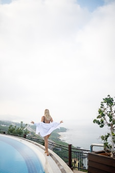 Bella donna in costume da bagno nero in posa vicino alla piscina all'aperto con vista mare