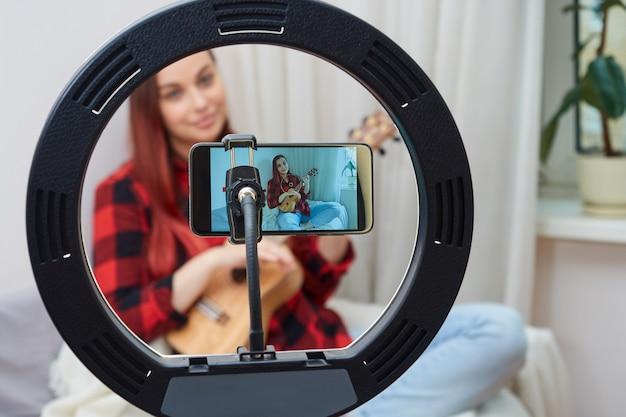 Bella blogger donna, musicista trasmette online, suona l'ukulele per i suoi abbonati. focus sullo smartphone