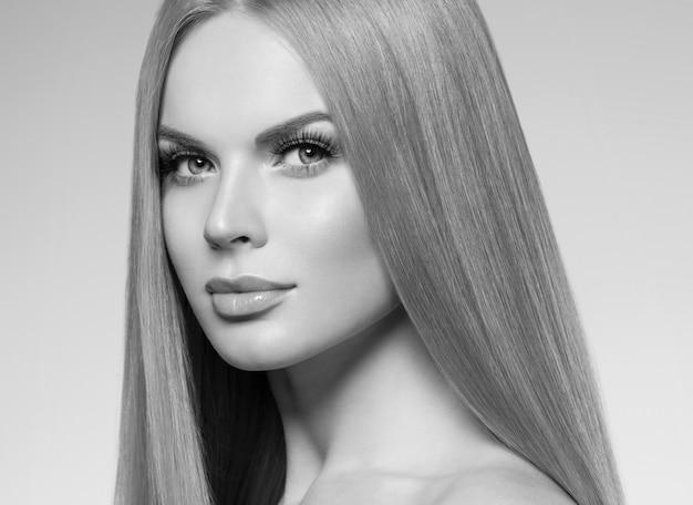 Bella donna bionda con trucco naturale capelli lunghi e concetto cosmetico pelle sana. colpo dello studio. monocromo. grigio. bianco e nero. colpo dello studio.