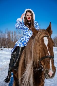 Bella donna in un cappotto blu a cavallo in inverno in una giornata di sole