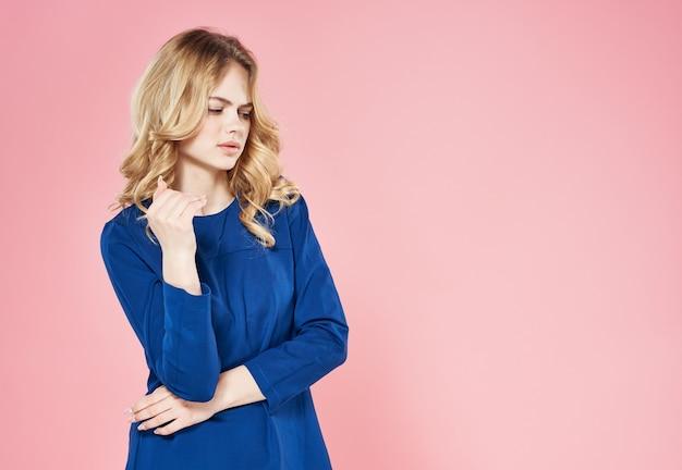 Bella donna in vestito blu ritagliata modello di sfondo rosa vista