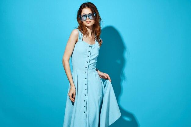 Bella donna in abito blu occhiali moda look attraente in posa ombra sullo sfondo. foto di alta qualità