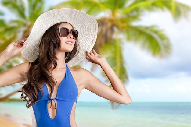 Bella donna in costume da bagno blu sullo sfondo del mare tropicale
