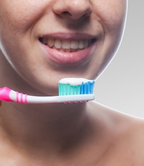 La bella donna che pulisce i suoi denti si chiude su. trattamenti mattutini