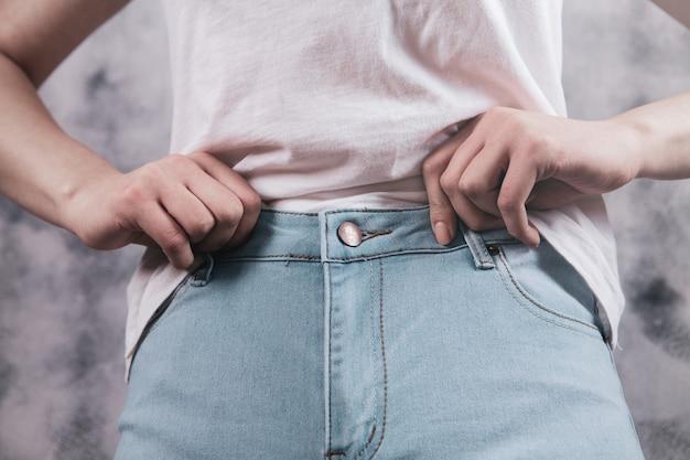 La bella donna abbottona le blue jeans