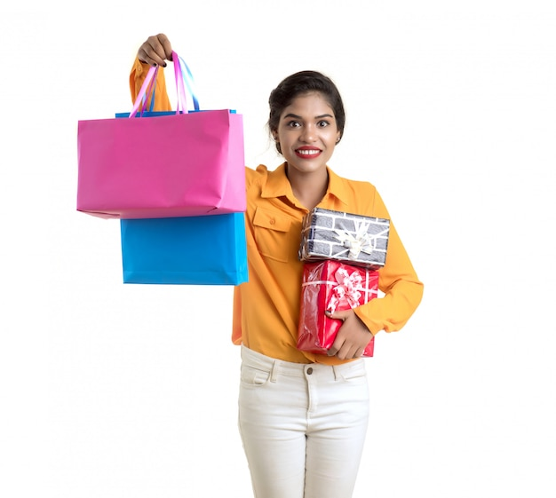 Bella donna che trasporta molti sacchetti della spesa e contenitore di regalo su una parete bianca.