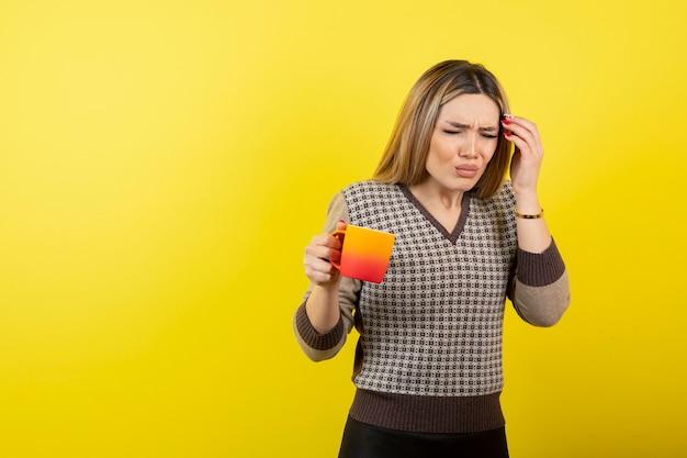 Bella donna in abito casual che tiene tazza di tè e che ha mal di testa.