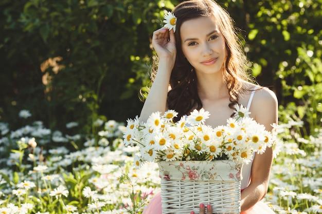 Bella donna nel campo della camomilla in estate. ragazza graziosa con il mazzo della camomilla nel cestino
