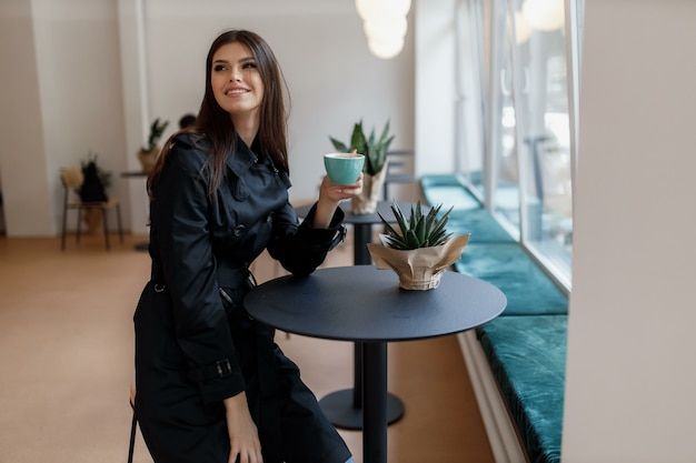 Bella donna in una caffetteria con una tazza di caffè.