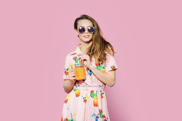 Bella donna in abito colorato con friuts stampati in posa con un bicchiere di succo
