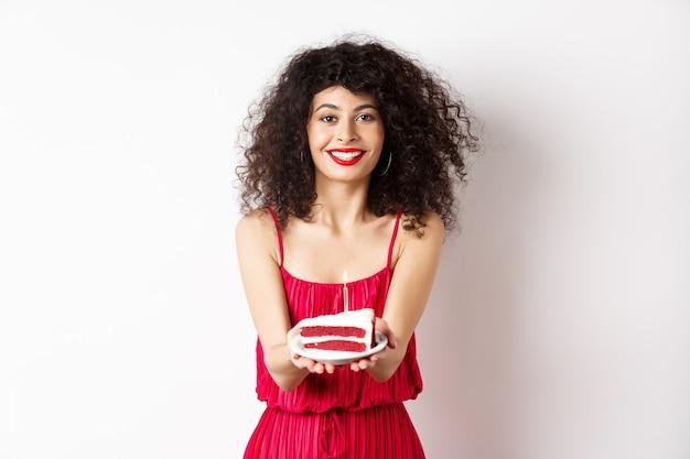 La bella donna si congratula con il compleanno, allunga la torta di compleanno con la candela e sorride, stando contro il fondo bianco.